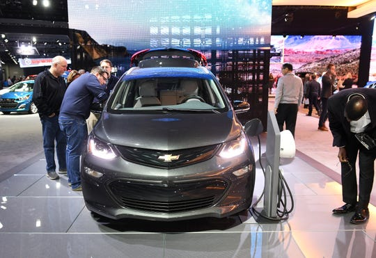 People check out the 2019 Chevrolet Bolt EV at the North American International Auto Show at Cobo Center in Detroit on Jan. 17, 2019.