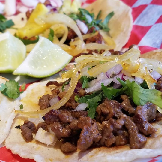 A carne asada taco (front) and a pork al pastor taco (rear) with lime, sauteed and fresh onions, cilantro and a side of fresh radishes at Lucy's Traditional Tex-Mex Restaurant.