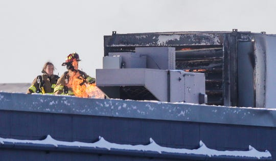 Fond du Lac Fire/Rescue members tend to a fire in an HVAC unit Wednesday, Jan 30, 2019 on top of Mercury Marine plant 15 on Pioneer Road in Fond du Lac.