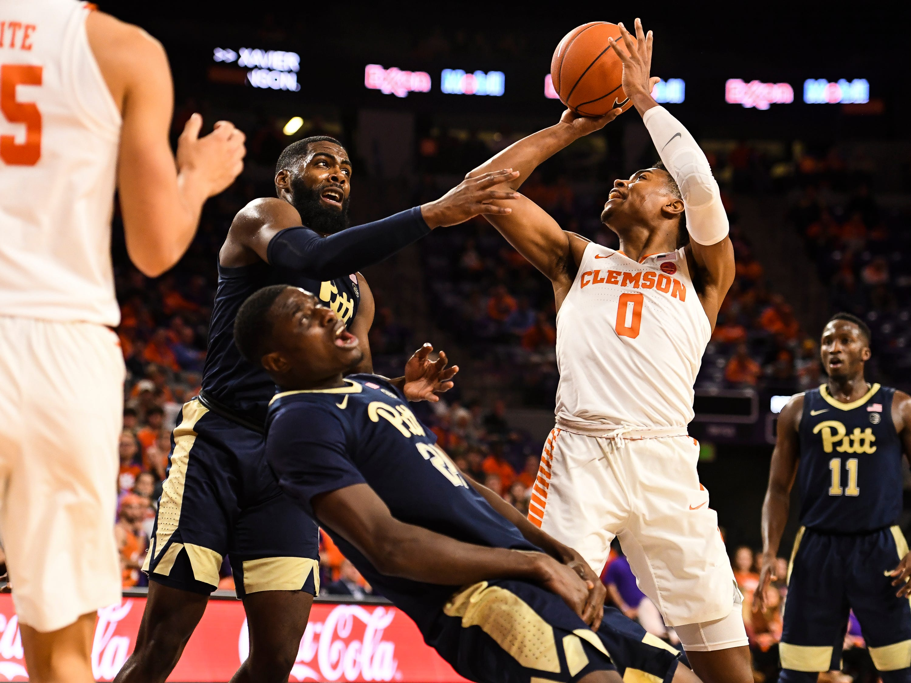 Clemson guard Clyde Trapp (0) attempts to shoot the ball as PittsburghÕs Jared Wilson-Frame (4) and Samson George (24) defend at Littlejohn Stadium on Tuesday, Jan. 29, 2019.