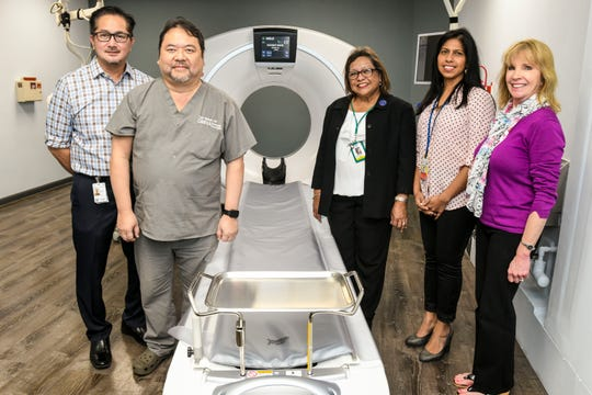 John Ilao, left, JMI Edison vice president, and Alyce Matlock, right, GE Healthcare clinical application specialist, gather with Dr. Tuan Nguyen, Guam Memorial Hospital Department of Radiology chairman; Lillian Perez-Posadas, GMH administrator and Nicole Dhanraj, GMH chief of radiology, in front of the newly installed GE Revolution EVO CT scanner at the Guam Memorial Hospital in Tamuning on Wednesday, Jan. 30, 2019.