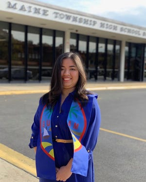 18-year-old Lydia Jovi Yanong Cruz, a former resident of Guam, proudly displays her island heritage in a sash sewn by her mother Carla Yanong. Cruz submitted an illustrated poster that won a district-wide art contest in Illinois, beating out over 500 entries.