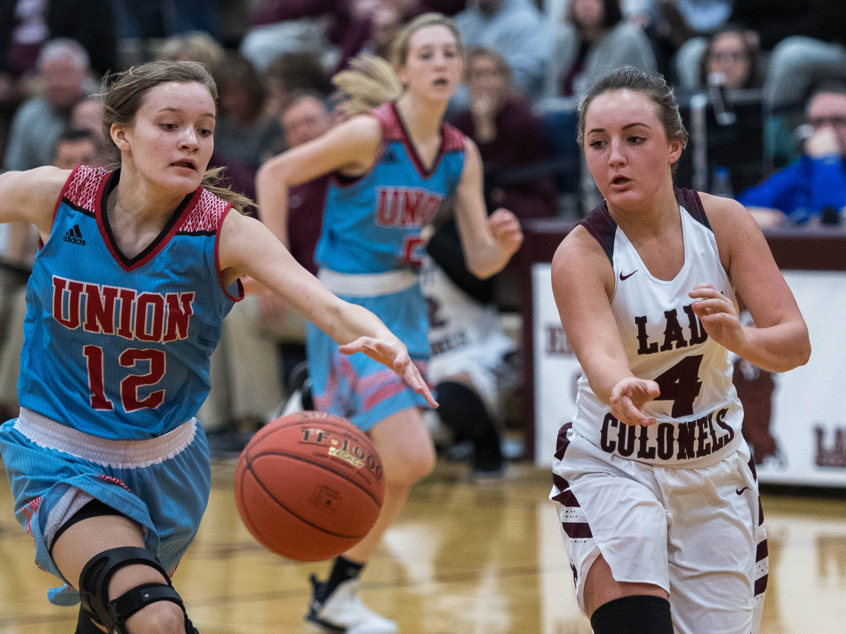 Raelle Beaven (12)  and Henderson County's Savannah Lacer (4) chase a loose ball as district rivals Union County Bravettes play the Henderson County Lady Colonels at Colonel Gym in Henderson Tuesday, January 29, 2019.