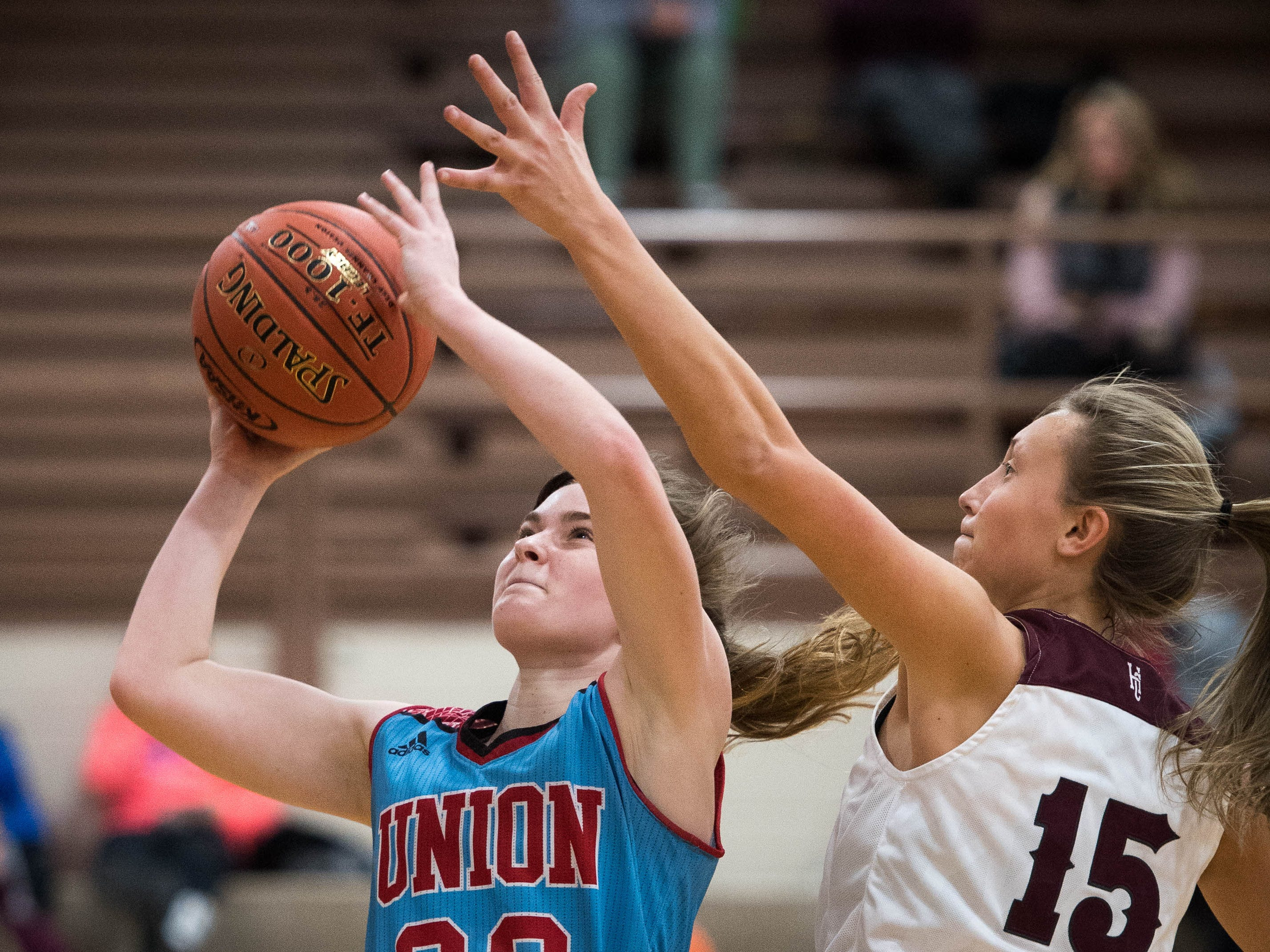 Jralee Roberson (22) shoots a layup under pressure from Henderson County's Alyssa Dickson (15) as district rivals Union County Bravettes play the Henderson County Lady Colonels at Colonel Gym in Henderson Tuesday, January 29, 2019.