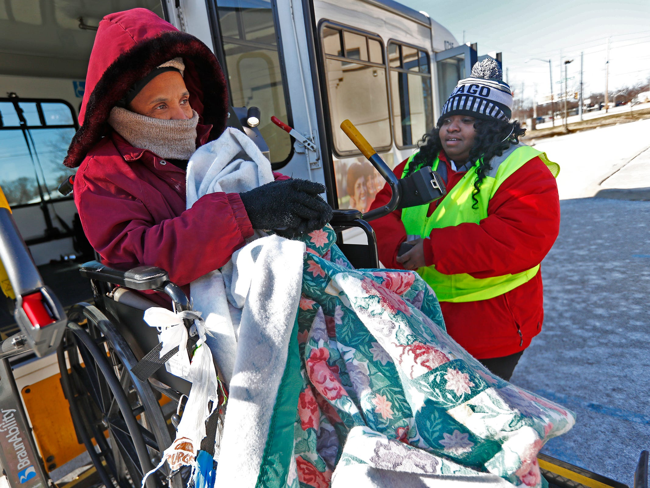Tara Drain, left, waits as Dee Francis, right, with IndyGo, helps her out of the bus to go into a Community Emergency Response Team warming center at the Municipal Gardens, 1831 Lafayette Rd., Wednesday, Jan. 30, 2019.  Drain was coming in out of the cold, as she doesn't have a home.  Wind chills made it feel like almost 30 below zero.