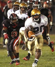 Bishop Dwenger running back Remound Wright (20) springs free for a 37-yard touchdown run that sealed the Saints' win.