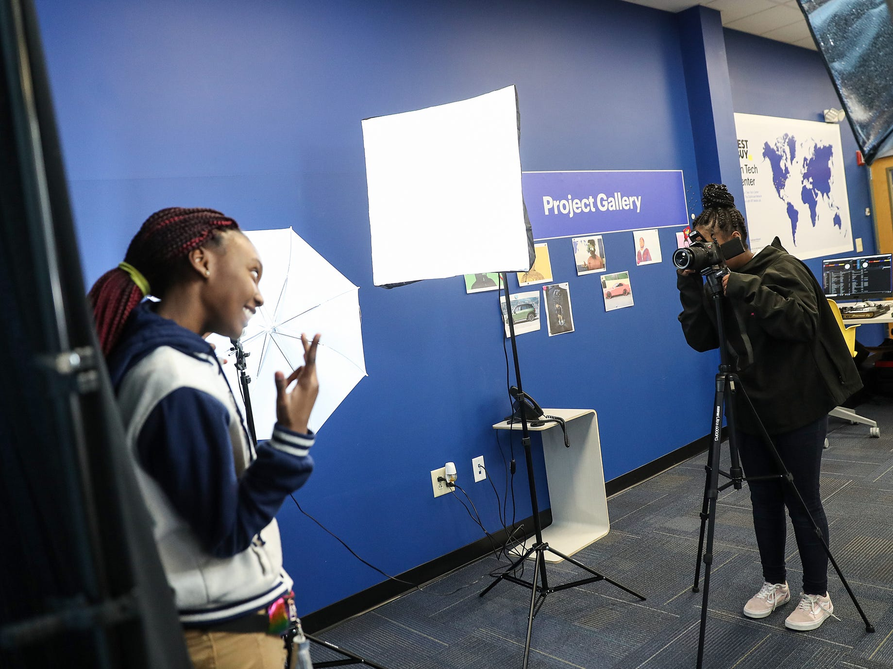 From left, Gabby Eaves, 13, poses for photos taken by Jamya Members, 12, during the opening of the Best Buy Teen Tech Center at the MLK Community Center in Indianapolis, Tuesday, Jan. 29, 2019.