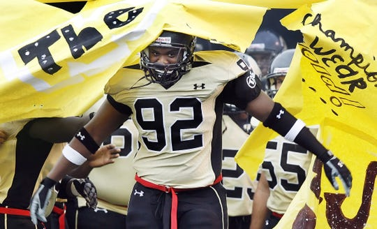 Kris Harley of Warren Central breaks through a paper sign as the team is introduced. Warren Central in 2008.