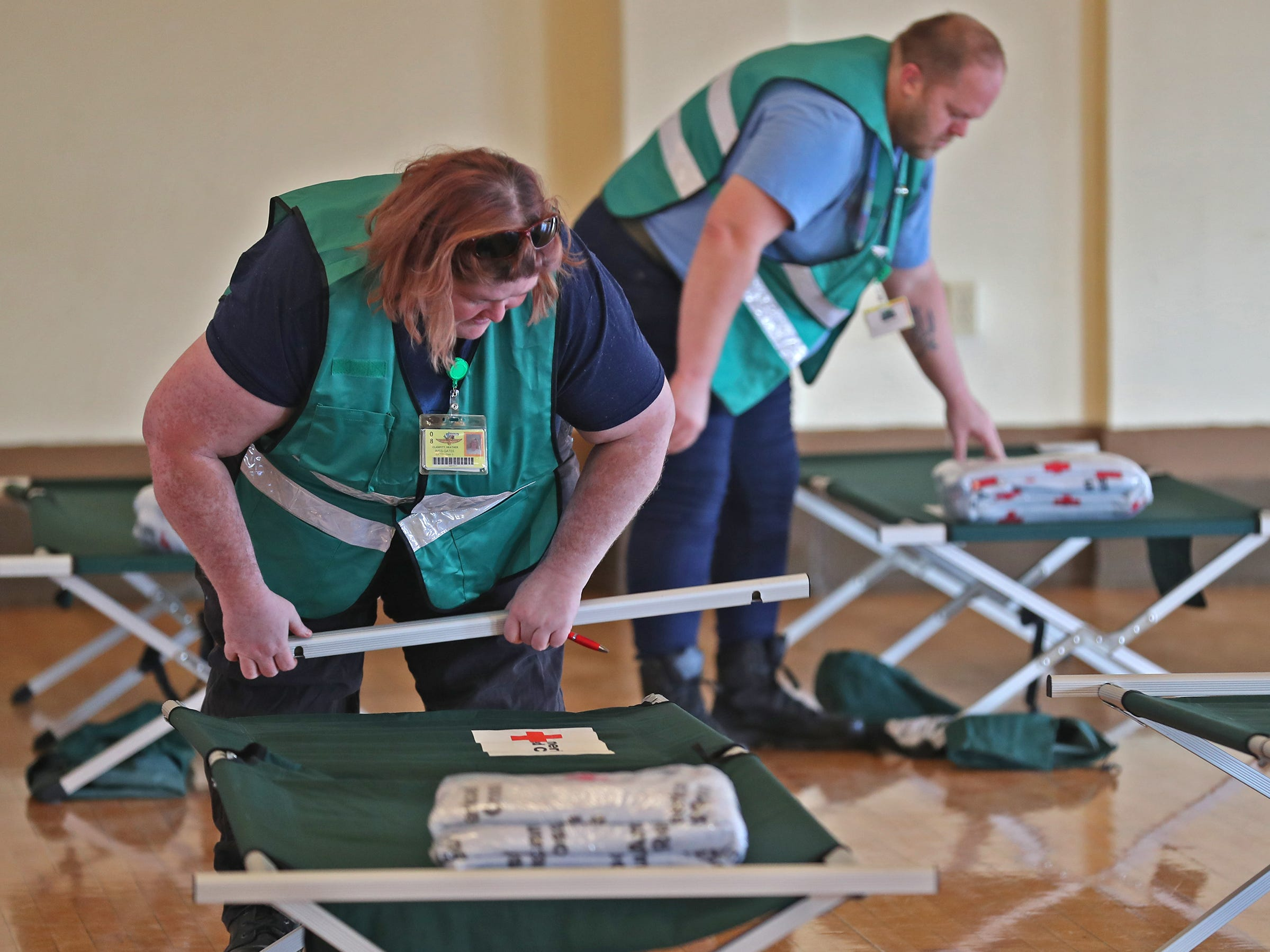 Heather Clampitt, left, and Joseph Clampitt, volunteers with CERT, fix cots at a Community Emergency Response 
