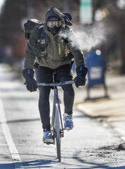 ClusterTruck bike courier Caylan Lanning calls it a day as he rides home following a very cold shift delivering food to hungry customers downtown Indianapolis on Wednesday, Jan. 30, 2019.
