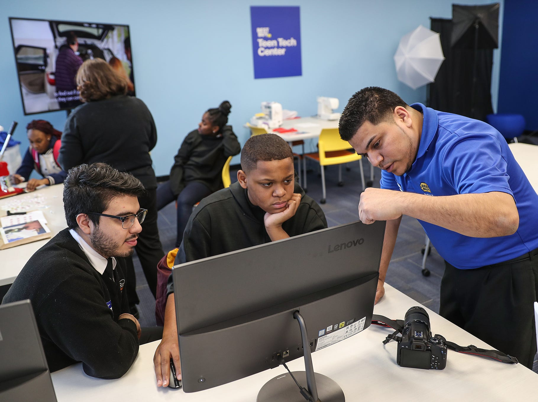 Carlos Bucio, left, and Yass Fernandez, right, teach photoshop skills to Damon Lee, 13, during the opening of the Best Buy Teen Tech Center at the MLK Community Center in Indianapolis, Tuesday, Jan. 29, 2019.