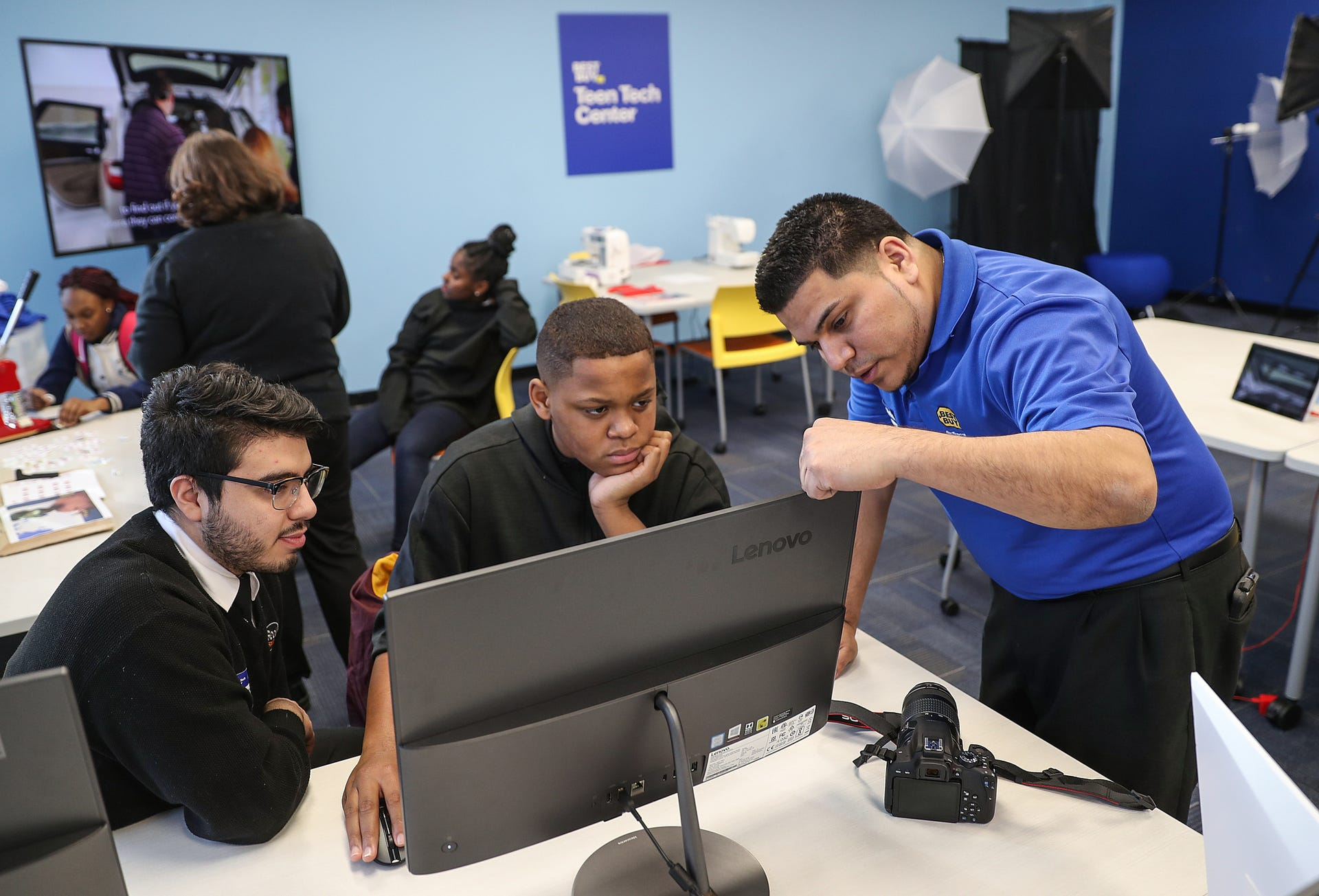 Carlos Bucio, left, and Yass Fernandez, right, teach photoshop skills to  Damon