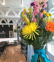 Flowers decorate the bright and airy dining room at Public Greens in downtown Indianapolis.