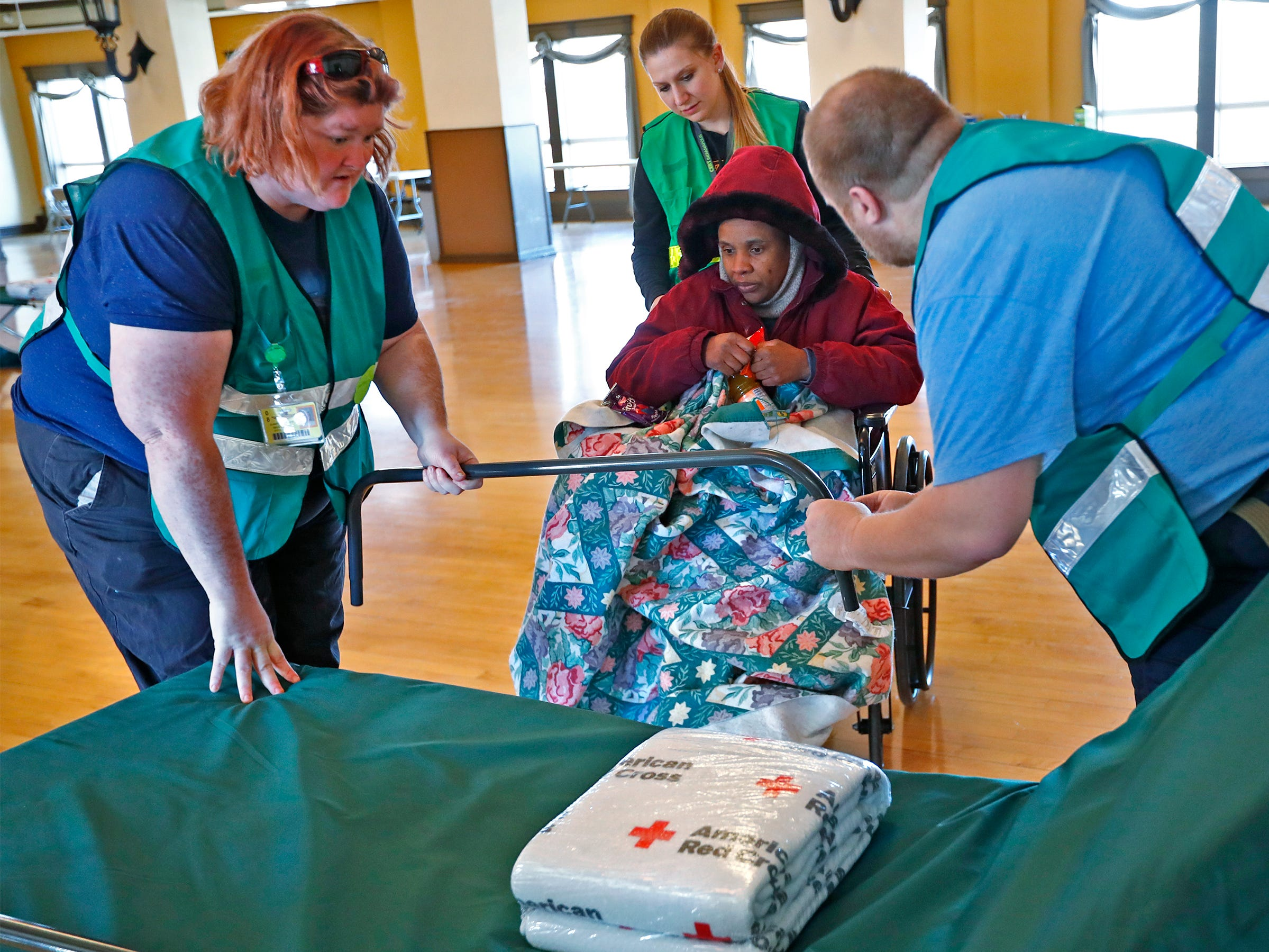 Tara Drain, center, being pushed by CERT volunteer Amanda Burris, waits as CERT volunteers Heather Clampitt, left, and Joseph Clampitt, right, ready a specialized cot for Drain, at a Community Emergency Response Team warming center at the Municipal Gardens, 1831 Lafayette Rd., Wednesday, Jan. 30, 2019.  Wind chills made it feel like almost 30 below zero.