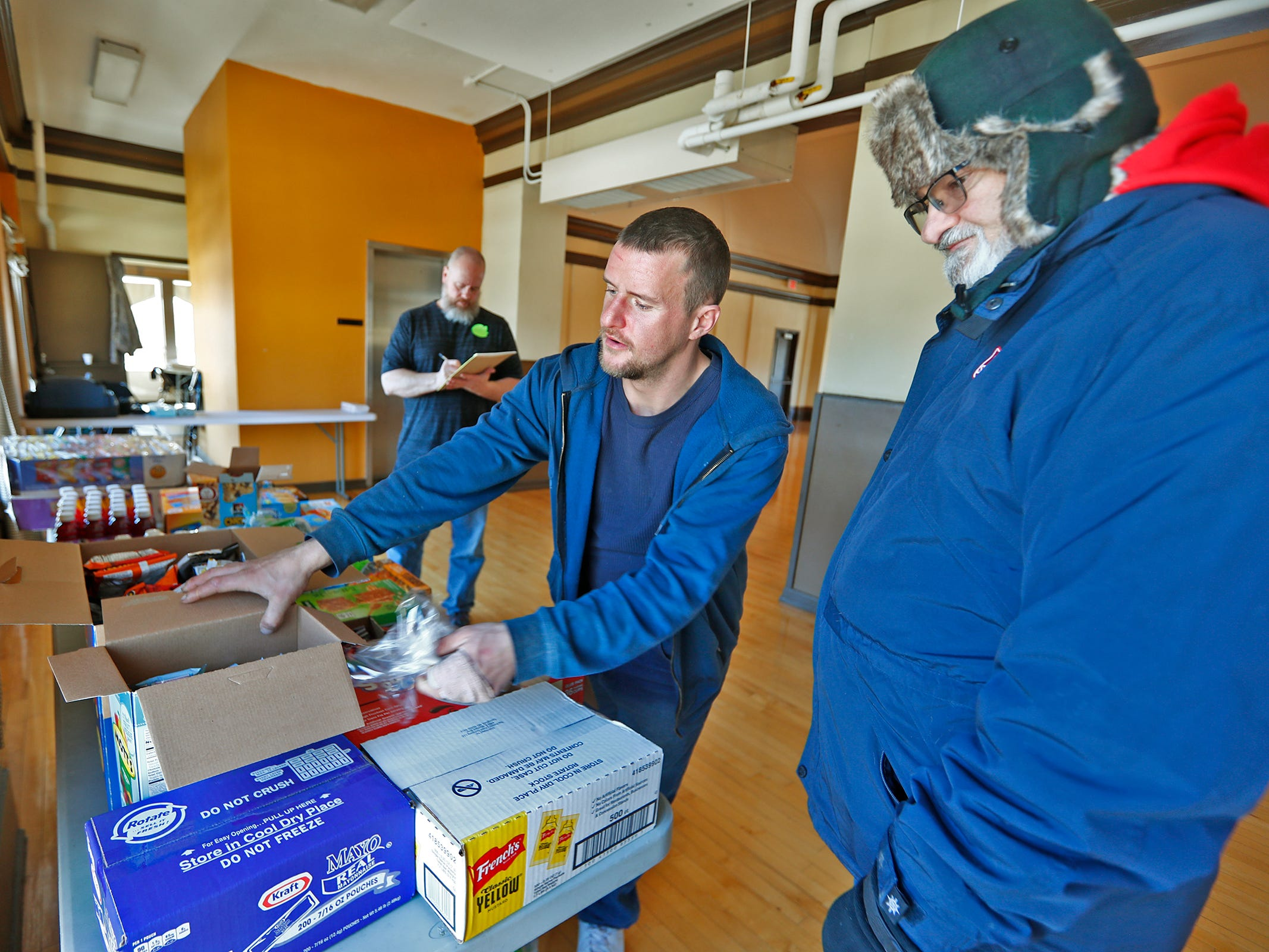 Salvation Army Major Keith Petrie, right, stands by as Chris Smith, center, grabs a snack at a Community Emergency Response Team warming center at the Municipal Gardens, 1831 Lafayette Rd., Wednesday, Jan. 30, 2019.  Petrie dropped off snacks from the Salvation Army. Wind chills made it feel like almost 30 below zero.