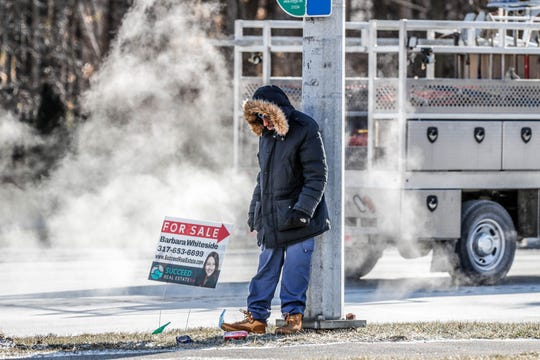 A man waits in sub-zero temperatures for the bus along north Michigan Rd. on Wednesday, Jan. 30, 2019.
