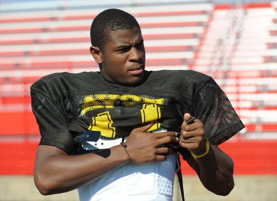 Avon's Armonze Daniel straps on his shoulder pads at a three-team football scrimmage at Pike, June 24, 2010.