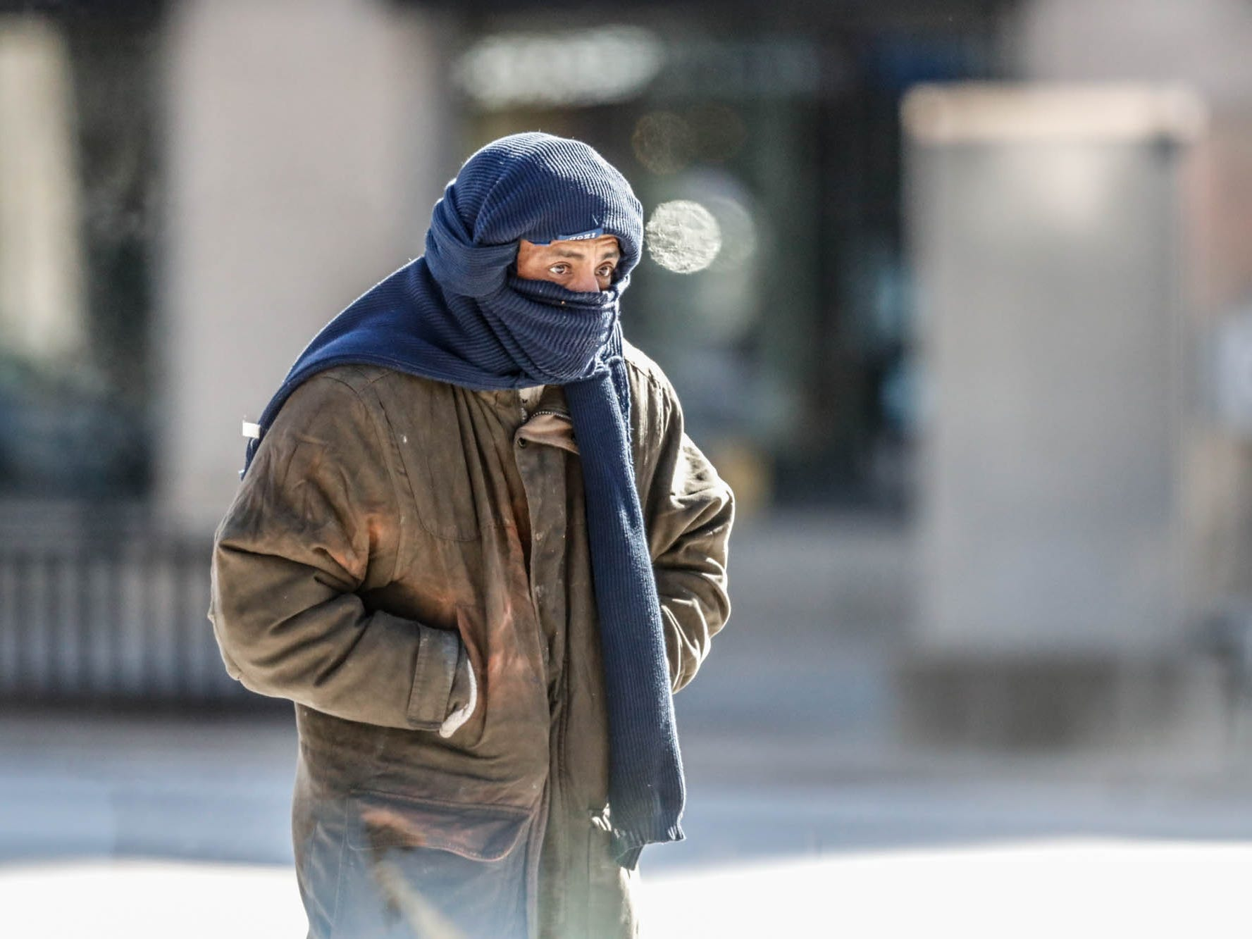 A man bundles up for the cold while walking in downtown Indianapolis on Wednesday, Jan. 30, 2019.