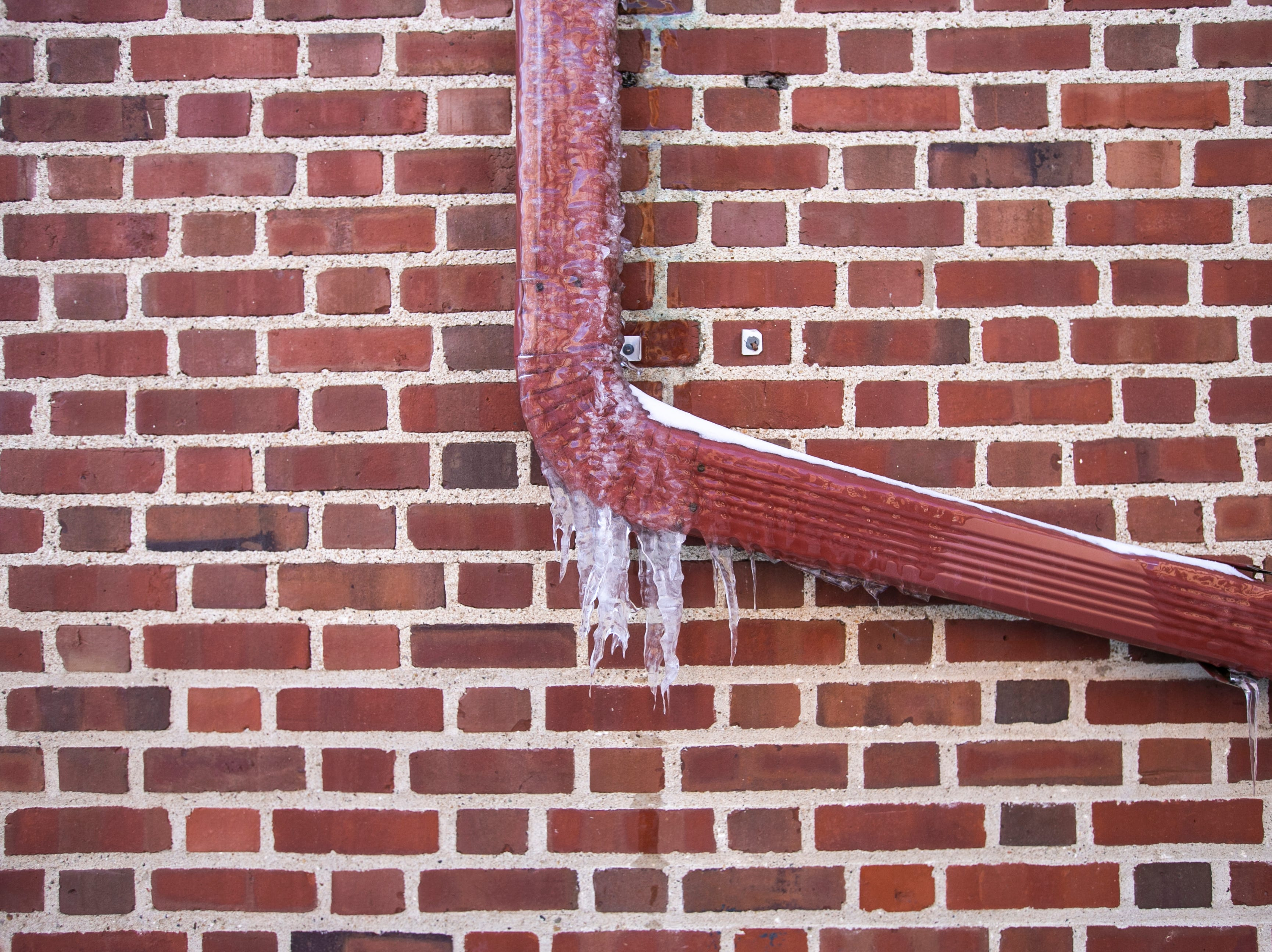 Icicles hang off of a downspout Wednesday, Jan. 30, 2019, on the east side of Halsey Hall on the University of Iowa campus in Iowa City, Iowa.