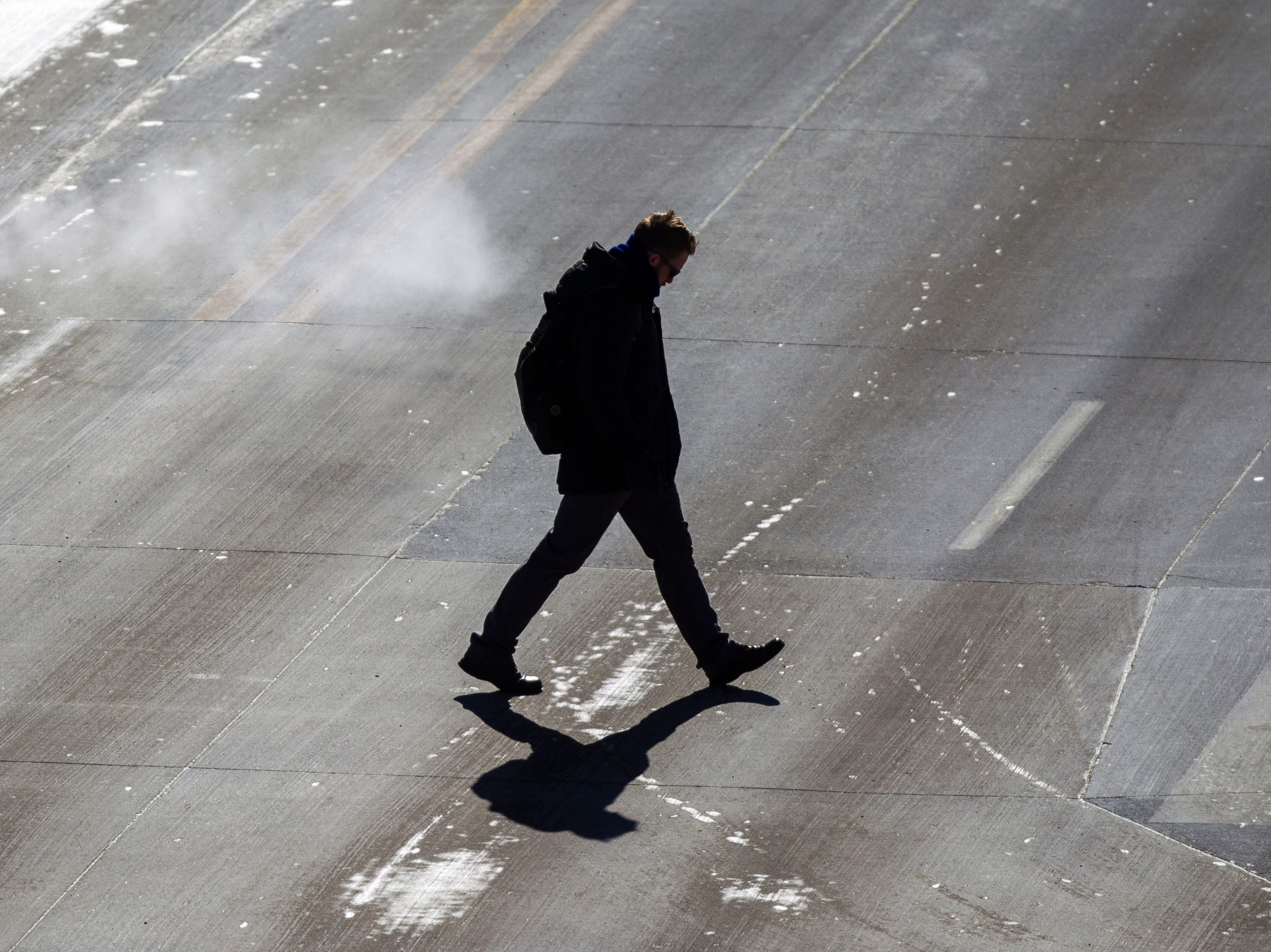 A person crosses Clinton Street on Wednesday, Jan. 30, 2019, in Iowa City, Iowa. Temperatures stayed below -10 degrees throughout the afternoon.