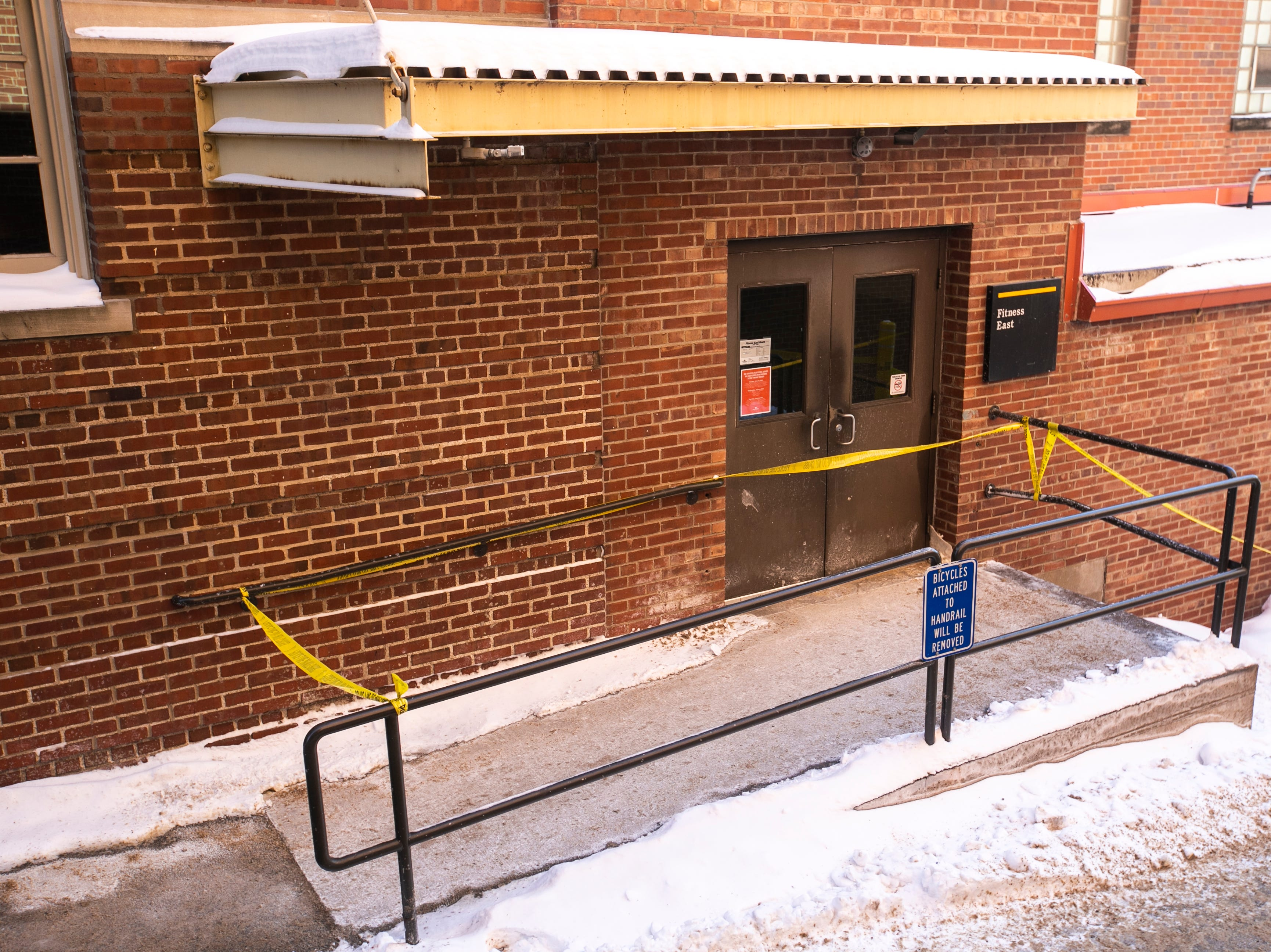 Yellow police tape cordons off an alleyway between the Iowa Memorial Union parking ramp and the door to Fitness East on the north side Halsey Hall, Wednesday, Jan. 30, 2019, on the University of Iowa campus in Iowa City, Iowa.