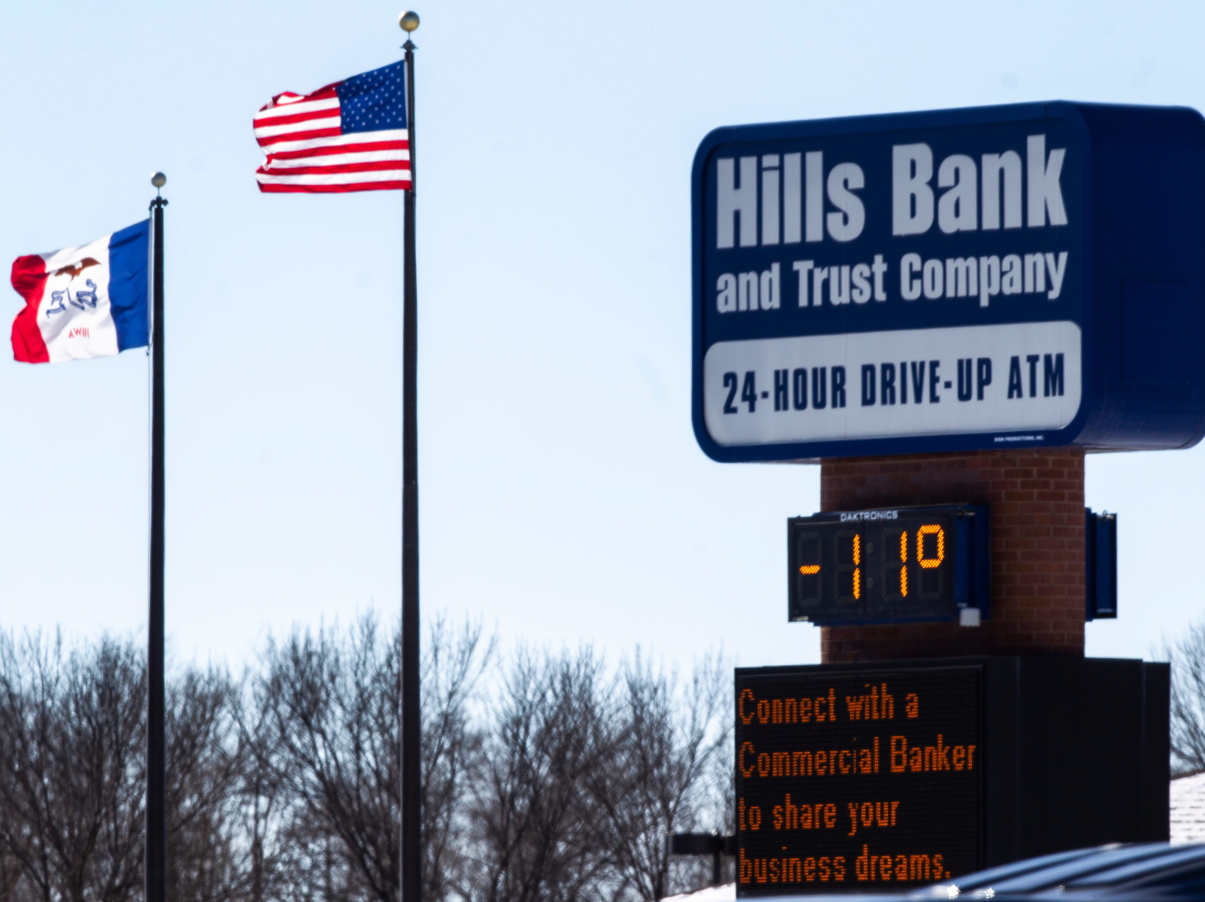 Flags wave behind a Hills Bank sign displaying -11 degrees on Wednesday, Jan. 30, 2019, along Highway 6 in Iowa City, Iowa.