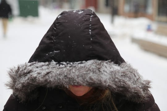 Chalene Fleming, of Pine City, hides underneath the hood of her coat during a cold Wednesday morning in Ithaca.