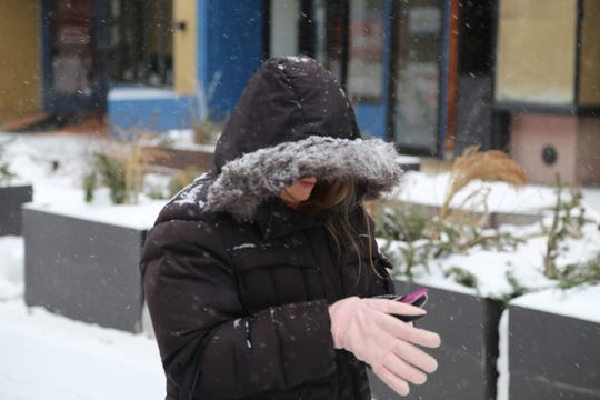 Chalene Fleming, of Pine City, uses her cellphone during a cold Wednesday morning in Ithaca.