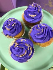 Purple frosting tops cupcakes at Kimmiesweett bakery.