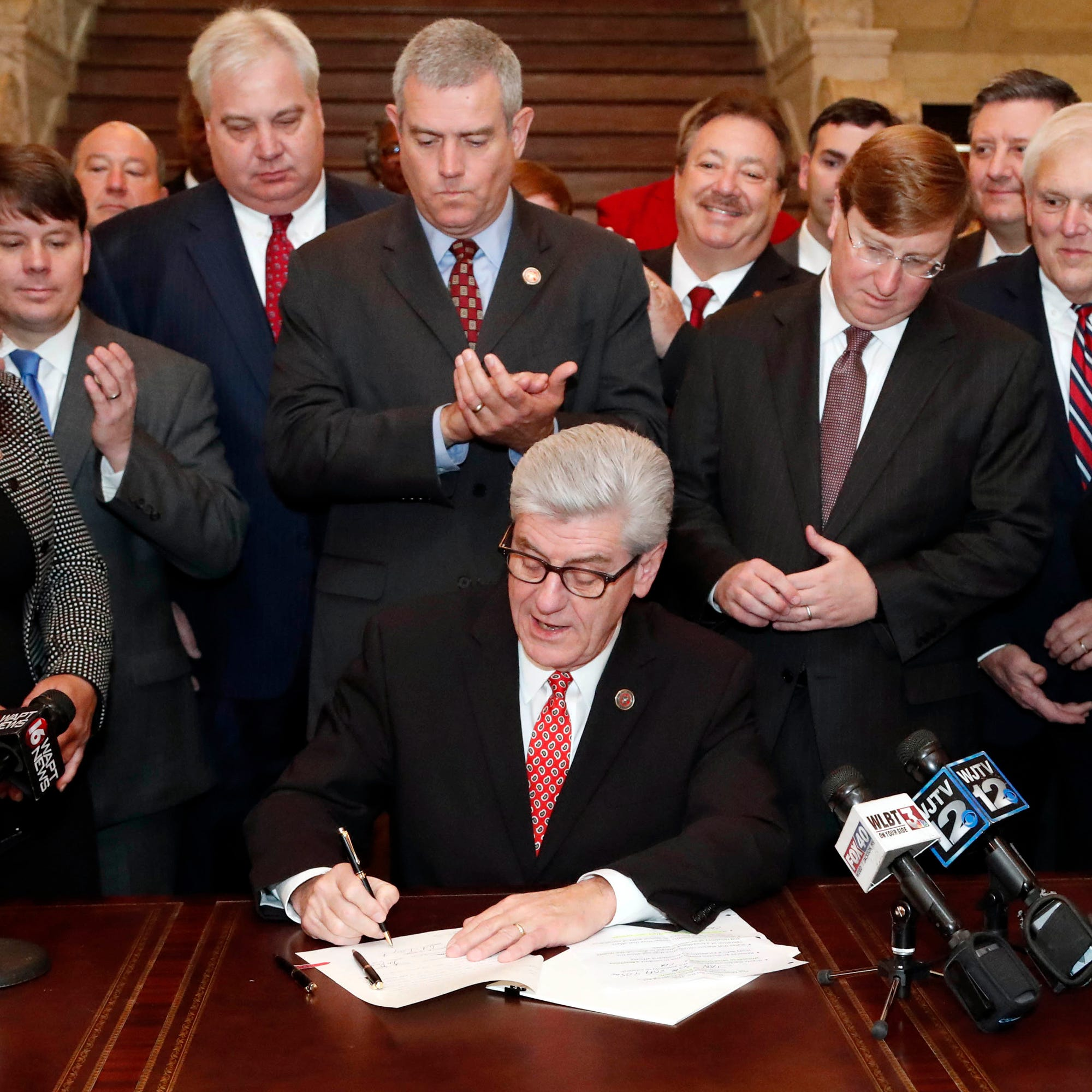 Gov. Phil Bryant, seated center, signs the Mississippi Broadband Enabling Act, as lawmakers and electric cooperatives officials applaud at the Capitol in Jackson, Miss., Wednesday Jan. 30, 2019. The measure allows Mississippi's 25 electric cooperatives to form subsidiaries to offer broadband internet service, removing a ban on the member-owned utilities getting into other businesses.