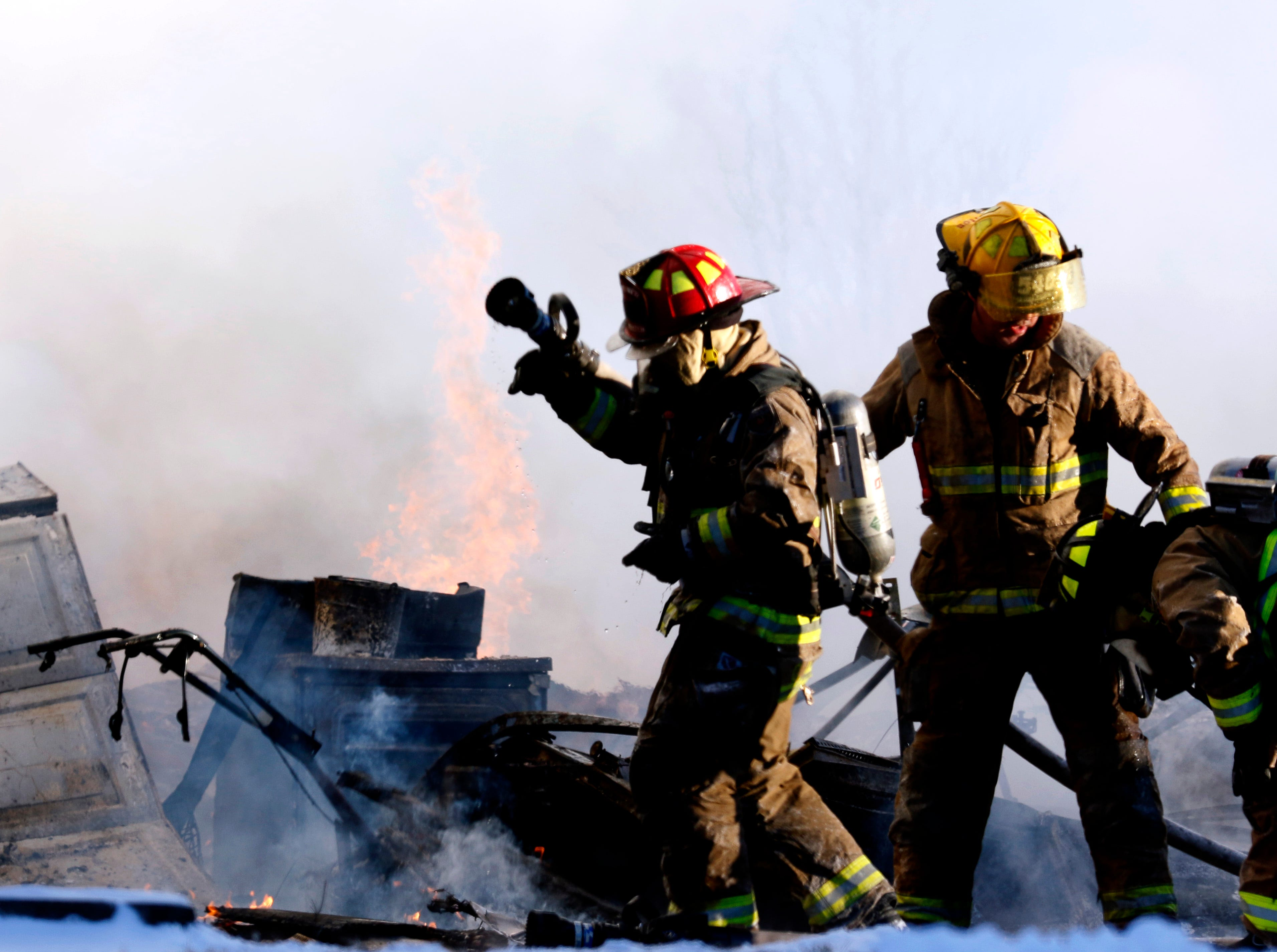Firefighters regroup as they fight a fire Wednesday, Jan. 30, 2019, at 9640 Old RUshville Road NE in Rushcreek Township. Bremen-Rushcreek Township Fire Chief William Duvall said the fire started in the home's garage, burning it to the ground, and spreading into the home itself. Duvall said the home, garage and several vehicles were total losses. No one was injured in the fire.