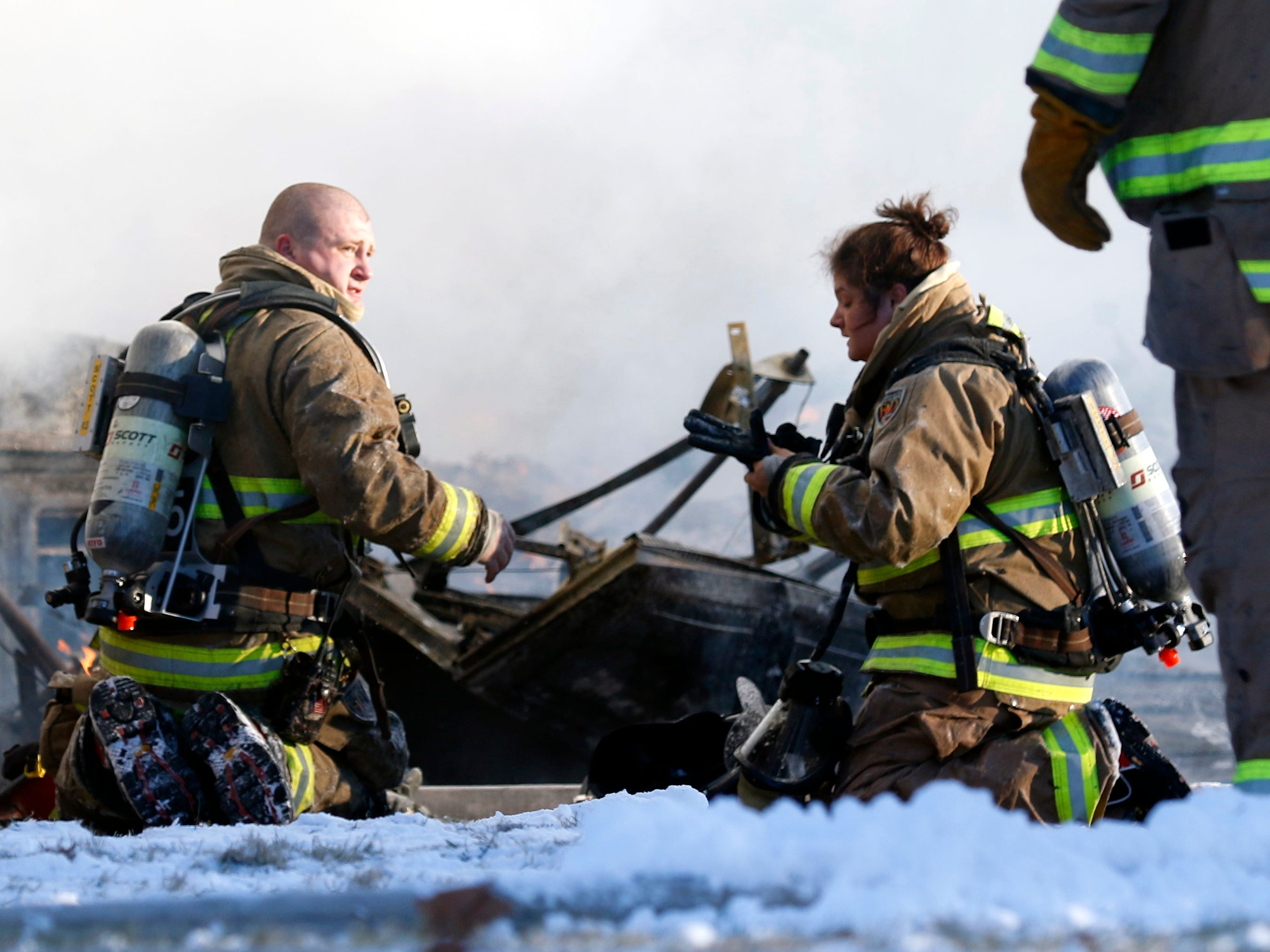 Firefighters rest in front what remains of a garage Wednesday, Jan. 30, 2019, at 9640 Old Rushville Road in Rushcreek Township. Bremen-Rushcreek Township Fire Chief William Duvall said the fire started in the home's garage, burning it to the ground, and spreading into the home itself. Duvall said the home, garage and several vehicles were total losses. No one was injured in the fire.