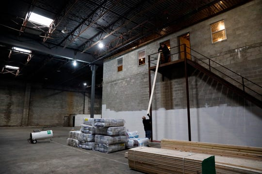 Workers lift a board into what will become office space in one of the warehouses on Fulkerson Avenue in Lancaster recently purchased by Shared Options.
