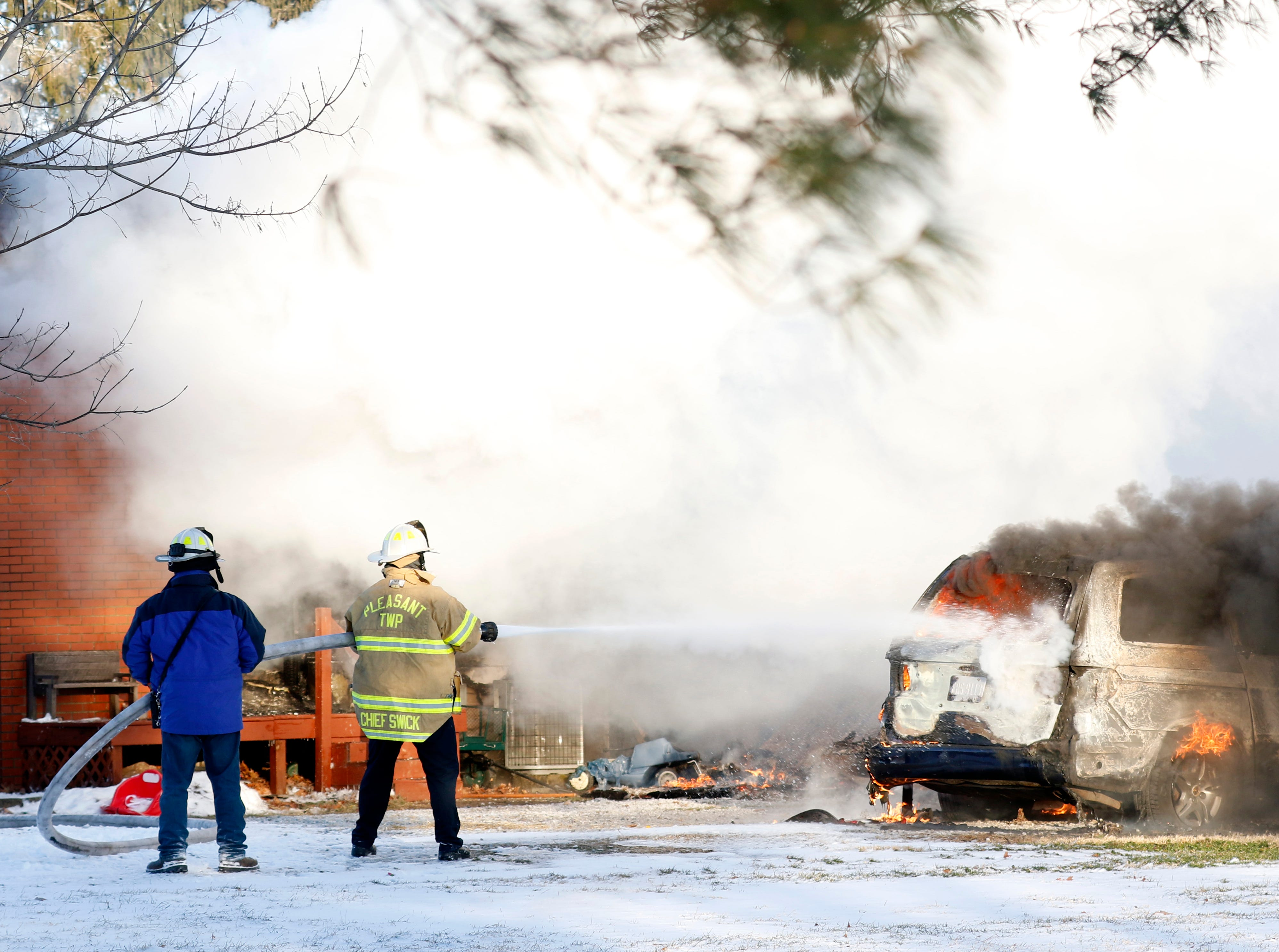 Pleasant Township Fire Department Asst. Chief Ralph Swick and Millersport Fire Chief Bob Price spray water on a burning vehicle Wednesday morning, Jan. 30, 2019, at 9640 Old Rushville Road in Rushcreek Township. Bremen-Rushcreek Township Fire Chief William Duvall said the fire started in the home's garage, burning it to the ground, and spreading into the home itself. Duvall said the home, garage and several vehicles were total losses. No one was injured in the fire.