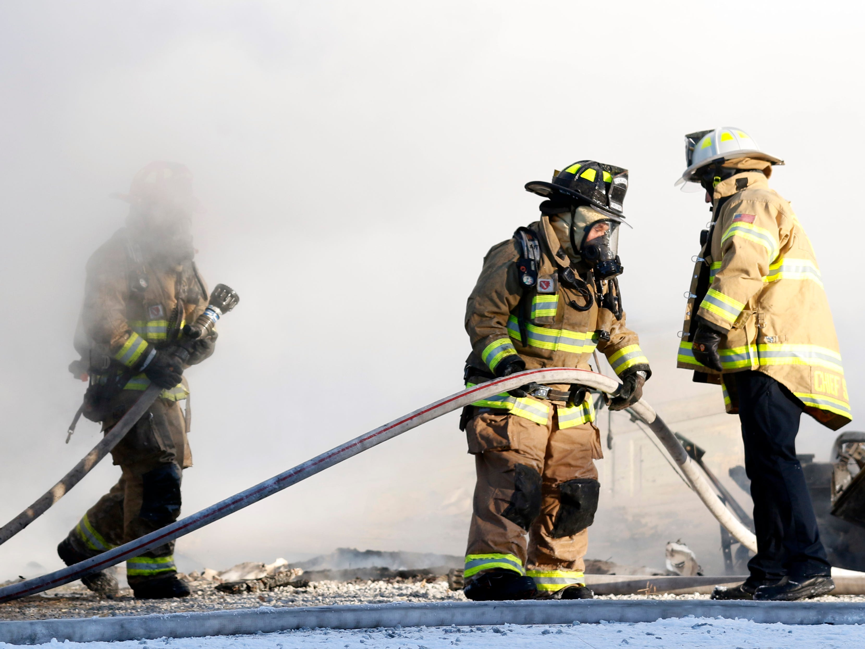 Firefighters walk through steam and smoke as they fight a fire at 9640 Old Rushville Road Wednesday, Jan. 30, 2019, in Rushcreek Township. Bremen-Rushcreek Township Fire Chief William Duvall said the fire started in the home's garage, burning it to the ground, and spreading into the home itself. Duvall said the home, garage and several vehicles were total losses. No one was injured in the fire.