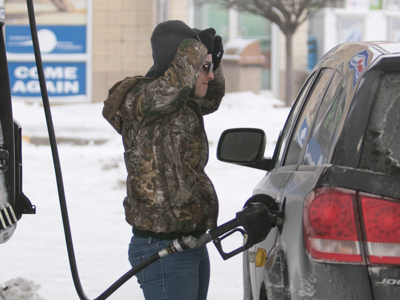 Filling her tank from the comfort from her vehicle's interior, Shelbey Carey of Lenawee County pulls her hood over her head to stay warm as she takes the nozzle out at the Marathon gas station at 1360 N. Burkhart Rd. Wednesday, Jan. 30, 2019.