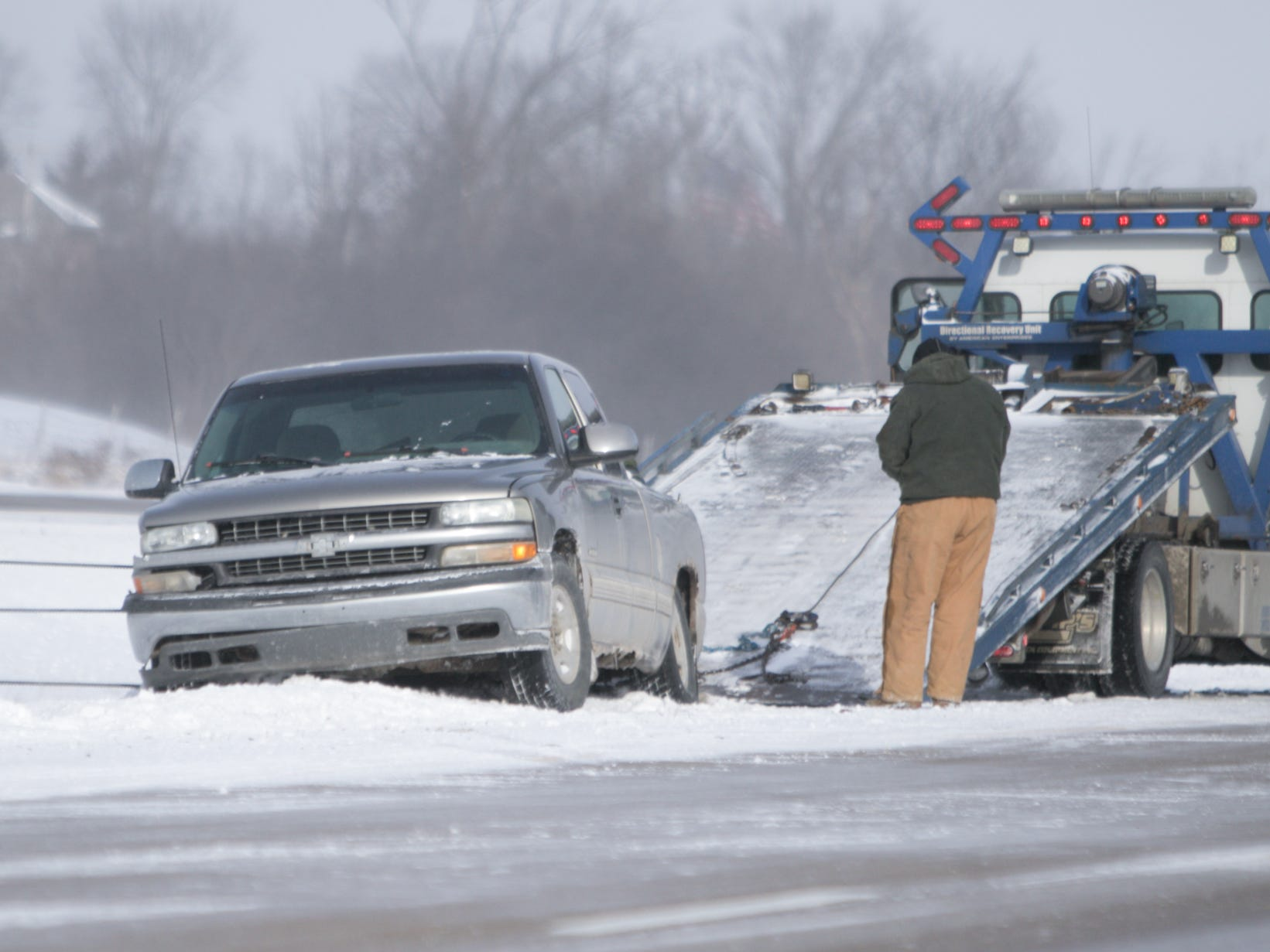 A tow truck driver hooks up a pickup truck to his flatbed, the pickup in the median of U.S. 23 facing opposite the direction of traffic Wednesday, Jan. 30, 2019 north of Clyde Rd. Icy roads and strong winds may have been factors in this and other accidents on the freeway Wednesday, Jan. 30, 2019.