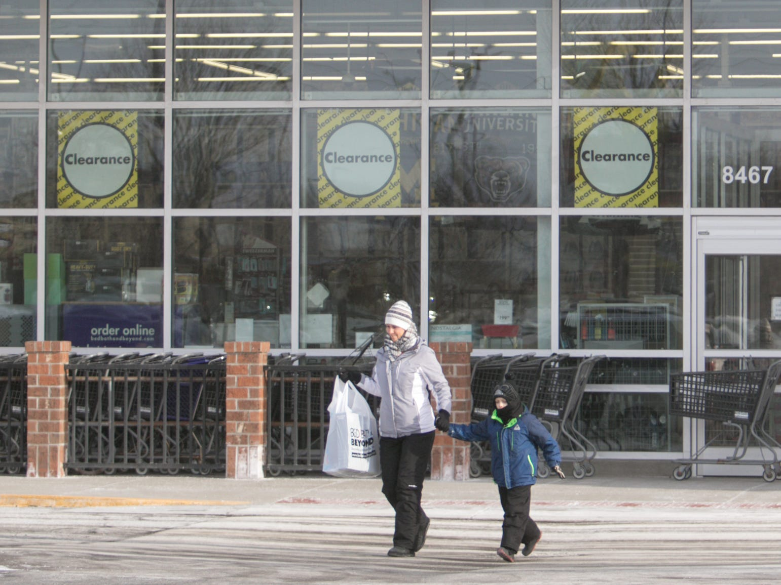 Shoppers hurry to their cars in the frigid weather Wednesday, Jan. 30, 2019, coming from the Bed, Bath and Beyond store at 8467 Grand River in Brighton.