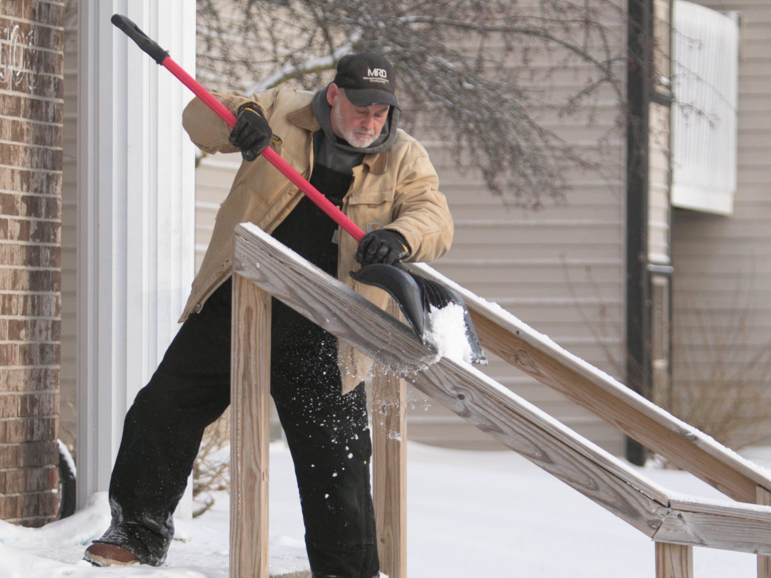 "Chris Konieczny, maintenance supervisor for Yorkshire Place Apartments in Howell, clears show from entryways at the apartment complex Wednesday, Jan. 30, 2019. Asked about how he deals with the sub-zero temperature, Konieczny said ""As long as I keep moving, I'm pretty good"""