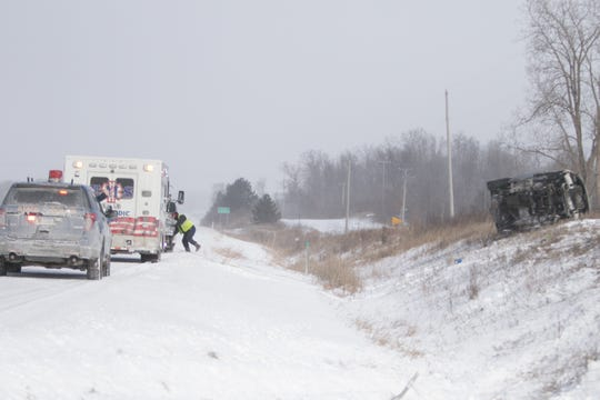 A Woody's Towing driver hooks up cables to a Jeep rolled over on the east embankment of northbound U.S. 23 north of Clyde Wednesday, Jan. 30, 2019.