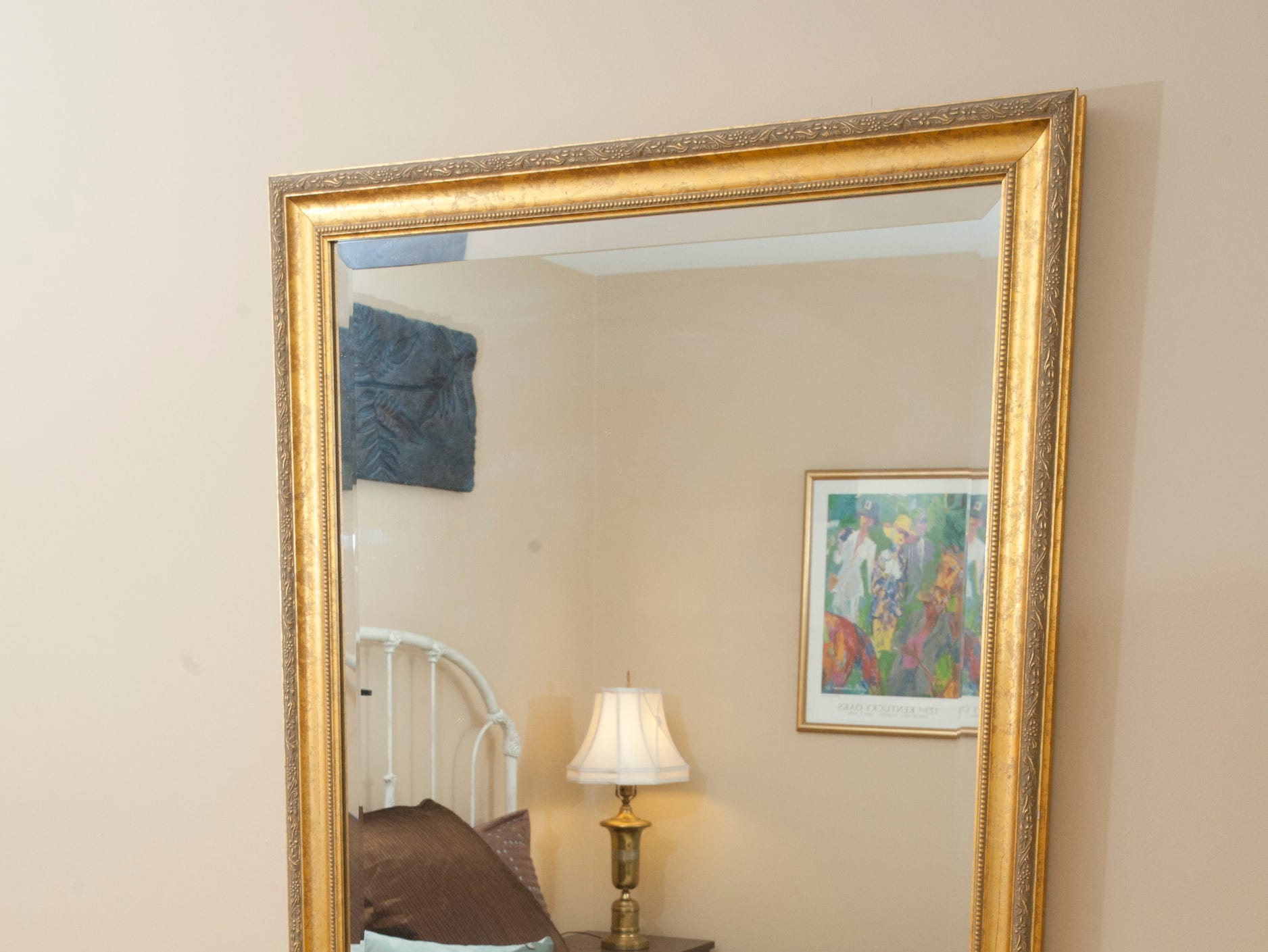 A mirror above a reading table reflects the bed in the home's second guest room.