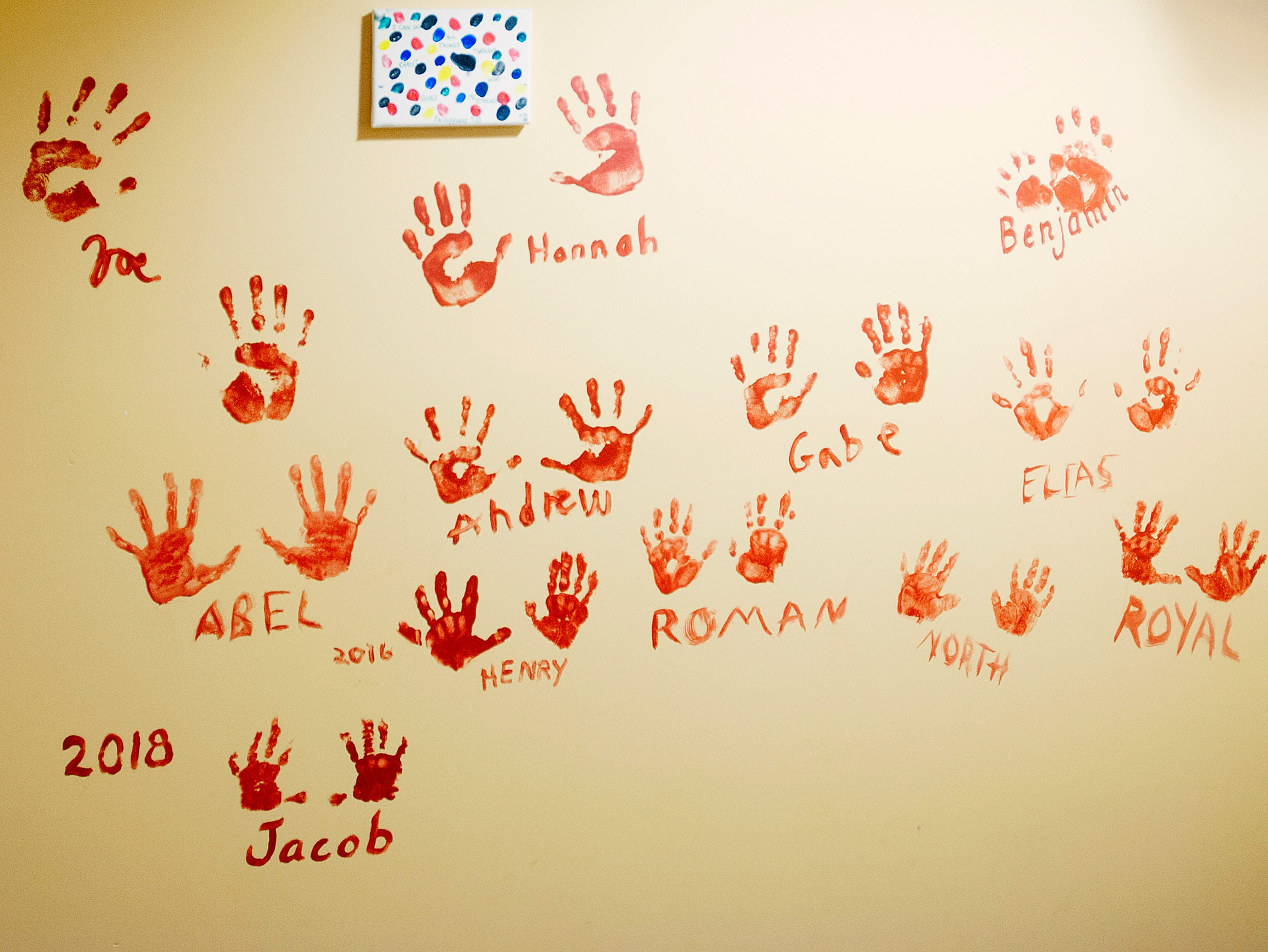 At the foot of the basement stairs, the Deebs keep a record of the handprints of all their grandchildren. 