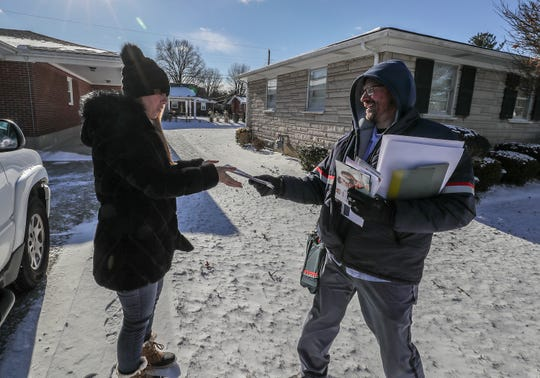 Mail carrier Paul Olges delivers the mail to Sarah Kelly on Tuesday with wind chill temperatures in the negative double digits. Jan. 30, 2019