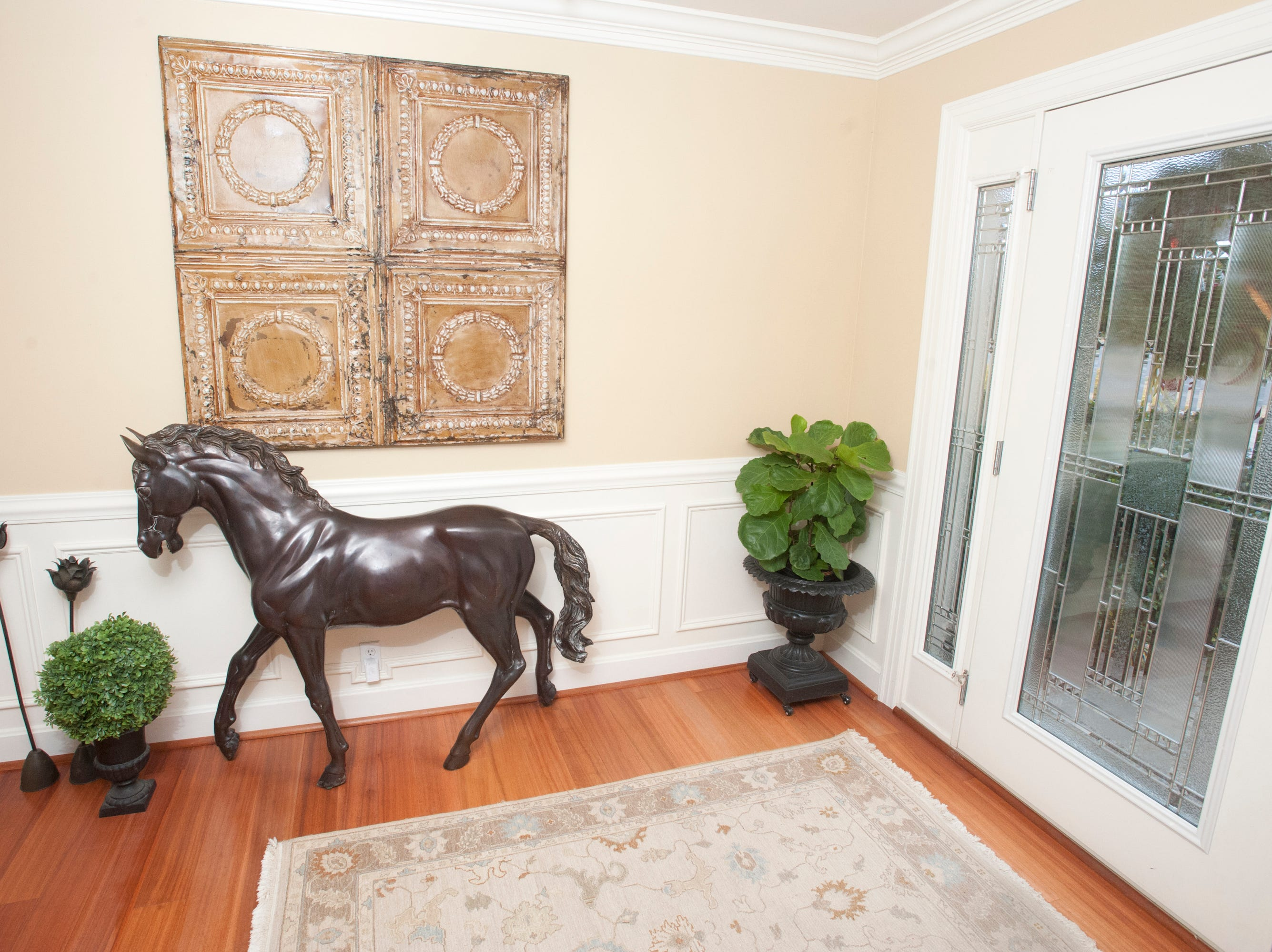 The entrance foyer of the home features a bronze horse by French sculptor P.J. Mene.