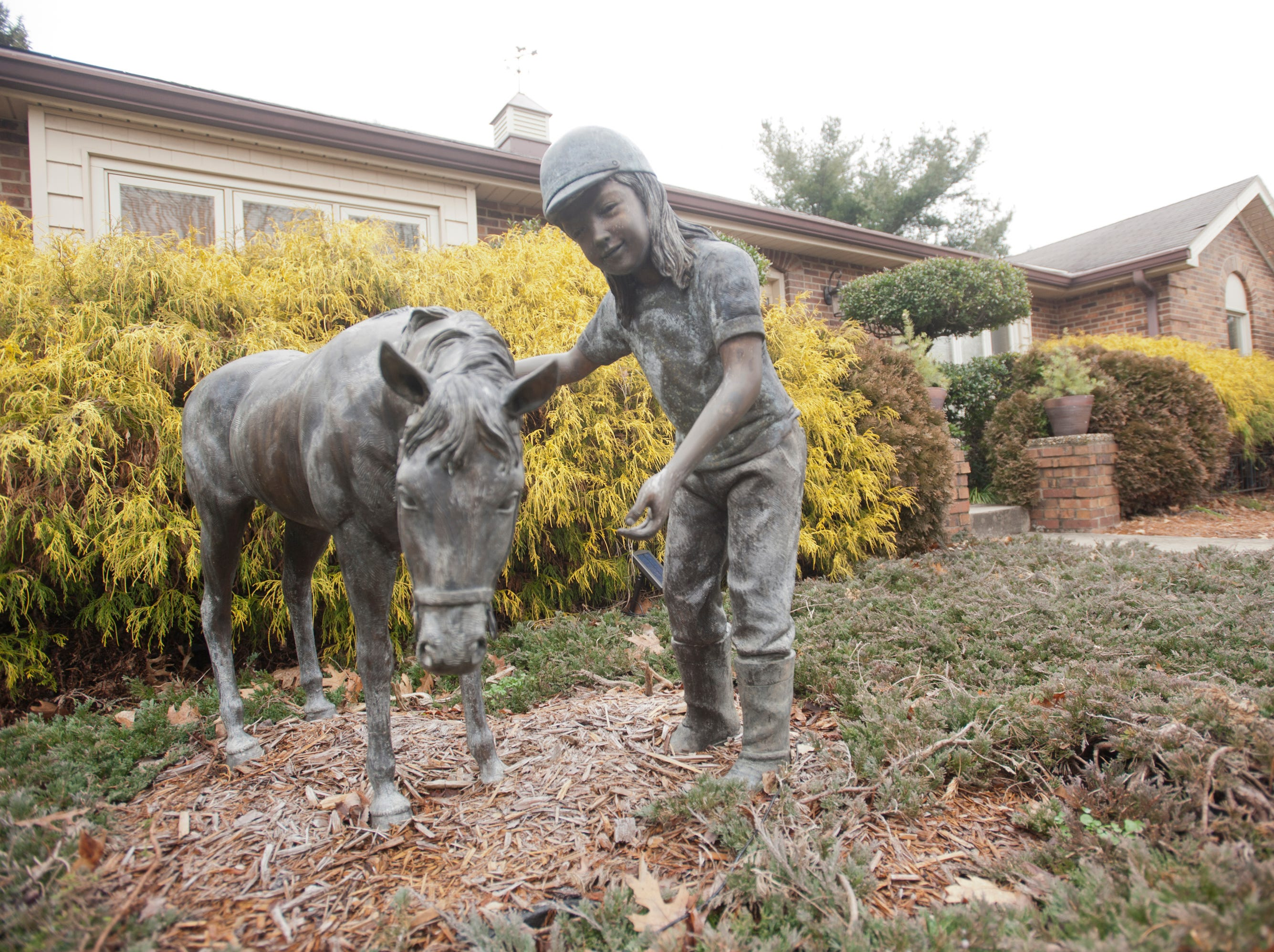 A sculpture of a horse and female adorn the front of the Deeb home in the Hurstbourne area of Louisville.