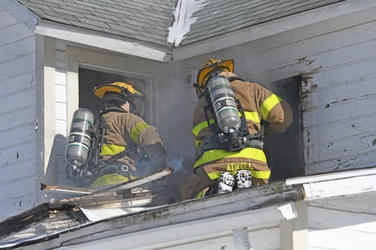 Mansfield firefighters battle a house fire Wednesday afternoon at Sixth and Sycamore streets.