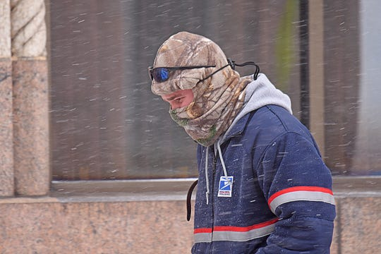 A United States Postal Service worker braves high winds and sub-zero temperatures on his route Wednesday morning in downtown Mansfield.