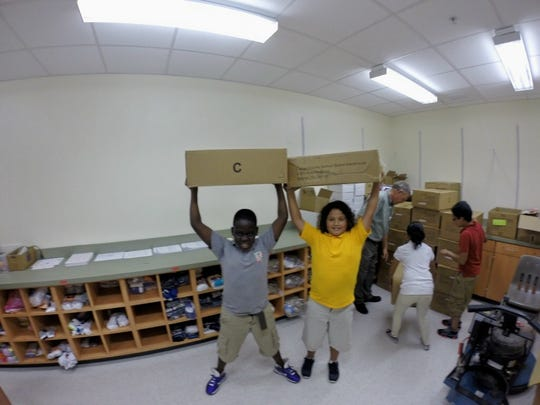 Parkside Elementary School counselor Tom Gemmer and Parkside fifth grade students unload boxes of clothing which had been donated by Angels Undercover.