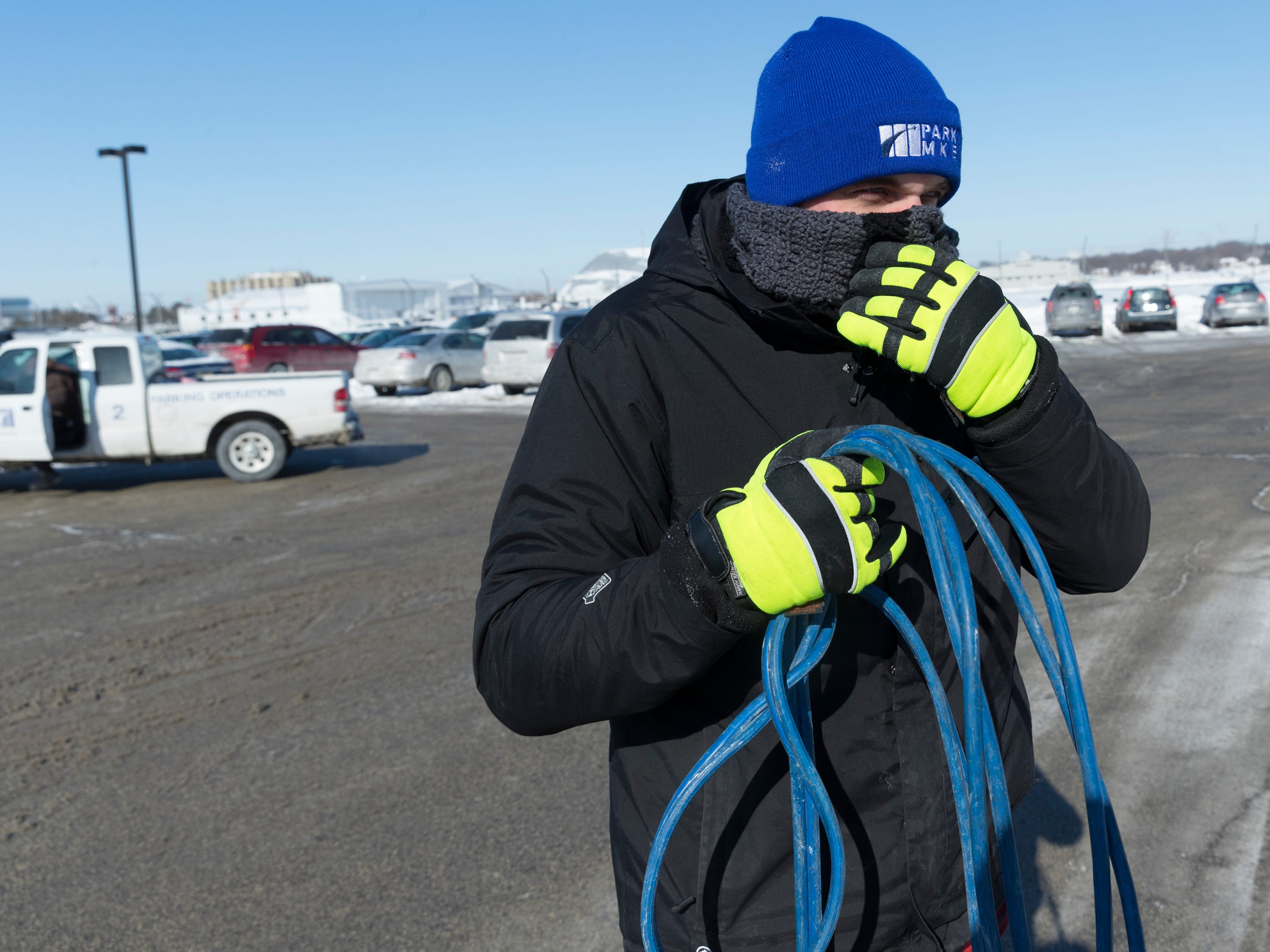 After helping jump-start a car, Jeff Plewa  walks to another car that needs a jump-start at Mitchell International Airport.