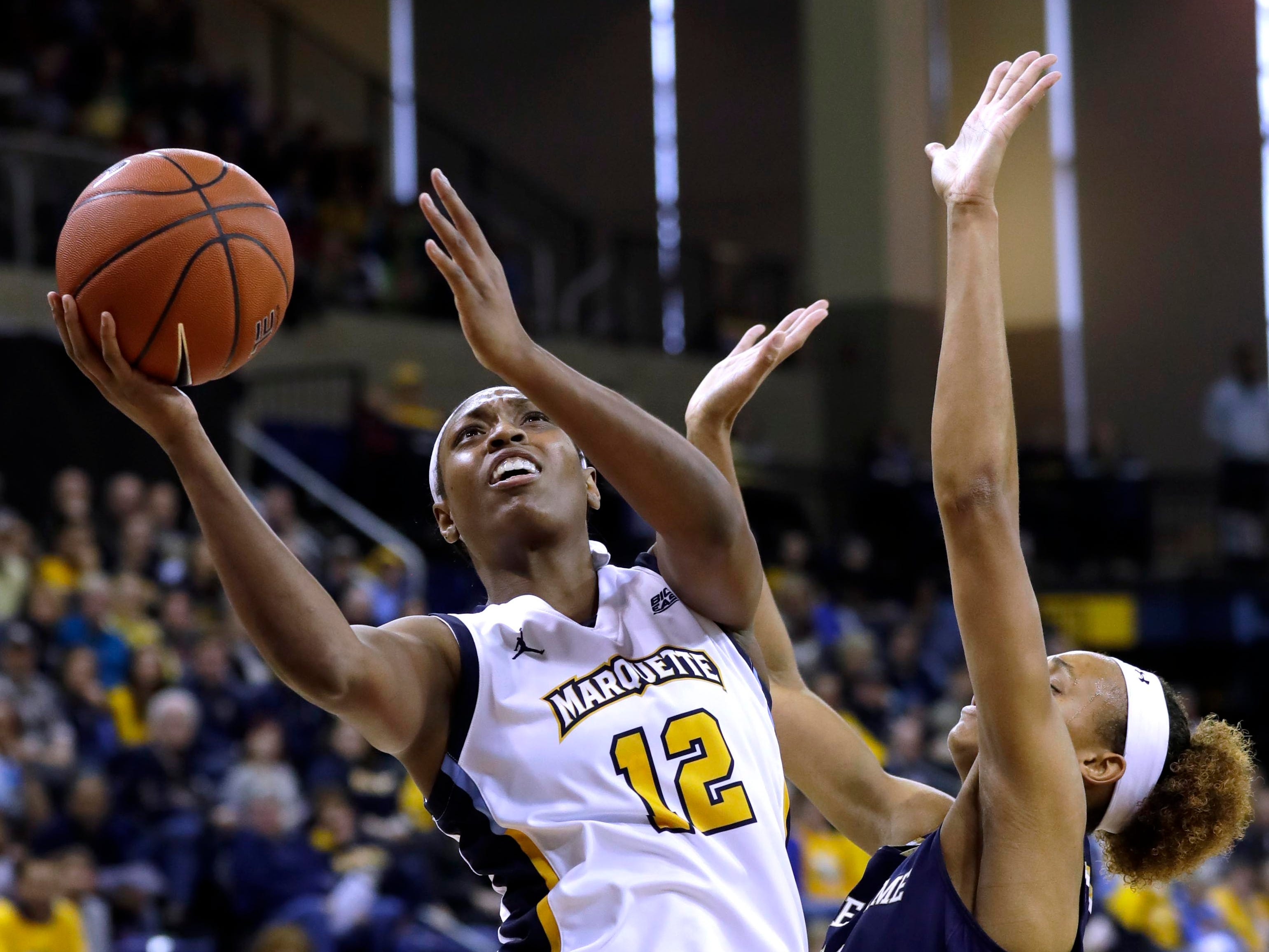 Marquette Golden Eagles forward Erika Davenport (12) scores on a drive to the basket against Notre Dame Fighting Irish forward Brianna Turner (11) during the women's basketball  game  between Marquette and Notre Dame. Notre Dame, the the defending national champion, which won the game 87-63, is led by former DSHA star Arike Ogunbowale. MU is also a top-25 team expected to win the Big East.   MILWAUKEE JOURNAL SENTINEL/RICK WOOD ORG XMIT: 20097356A